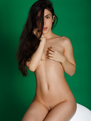 Luna's long and slender body stands out against the plain green background, her long black hair draping gently over her delicate shoulders as she poses and flirts for her debut series.
